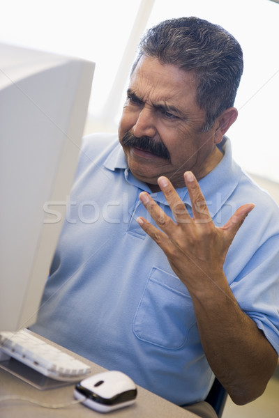 Mature male student expressing frustration at computer Stock photo © monkey_business