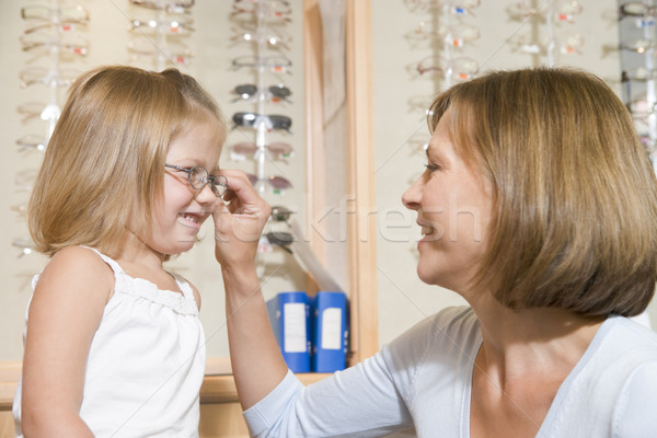 Woman trying eyeglasses on young girl at optometrists smiling Stock photo © monkey_business