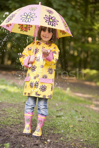 Young girl outdoors in rain with umbrella smiling Stock photo © monkey_business