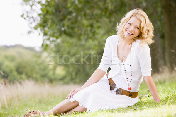 Stock photo: Woman sitting outdoors smiling