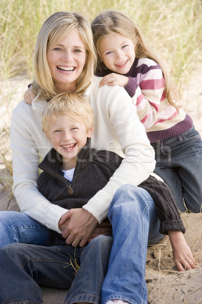 Mother and two young children sitting on beach smiling Stock photo © monkey_business