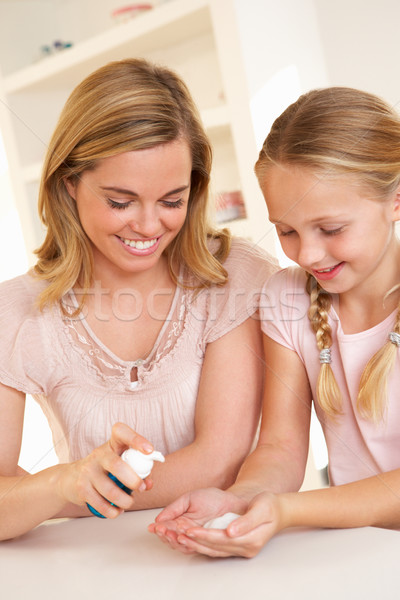 Mother putting sanitizer on young girl's hands Stock photo © monkey_business