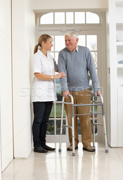 Stock photo: Carer Helping Elderly Senior Man Using Walking Frame