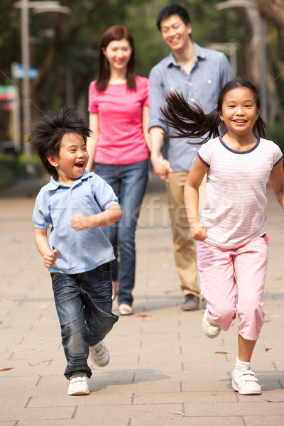 Stock photo: Chinese Family Walking Through Park With Running Children