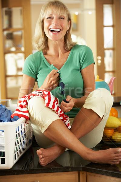 Senior Woman Sorting Laundry In Kitchen Stock photo © monkey_business