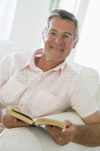 Stock photo: Man in living room reading book smiling