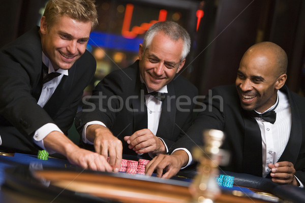 Groupe Homme amis roulette table casino Photo stock © monkey_business