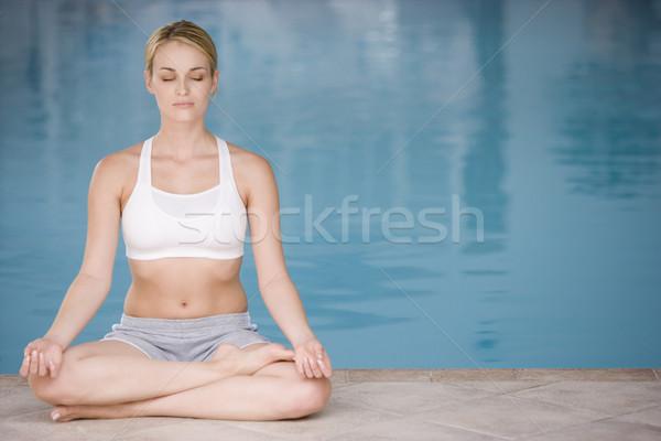 Woman sitting poolside doing yoga Stock photo © monkey_business