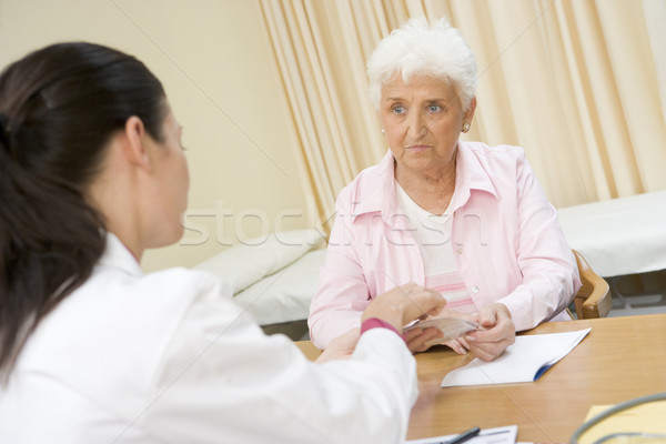 Stock photo: Woman in doctor's office frowning