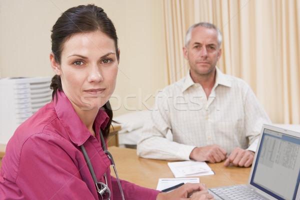 Doctor with laptop and man in doctor's office frowning Stock photo © monkey_business