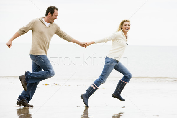 Couple running on beach holding hands smiling Stock photo © monkey_business