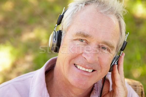 Idős férfi fejhallgató kert zöld szék Stock fotó © monkey_business