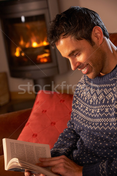Middle Aged Man Relaxing With Book By Cosy Log Fire Stock photo © monkey_business