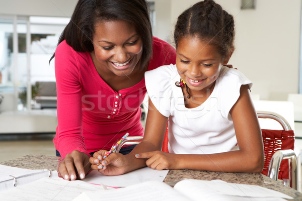 Stock photo: Mother Helping Daughter With Homework In Kitchen
