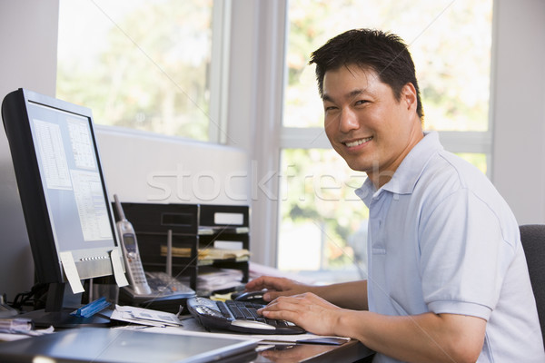 Man in home office using computer and smiling Stock photo © monkey_business