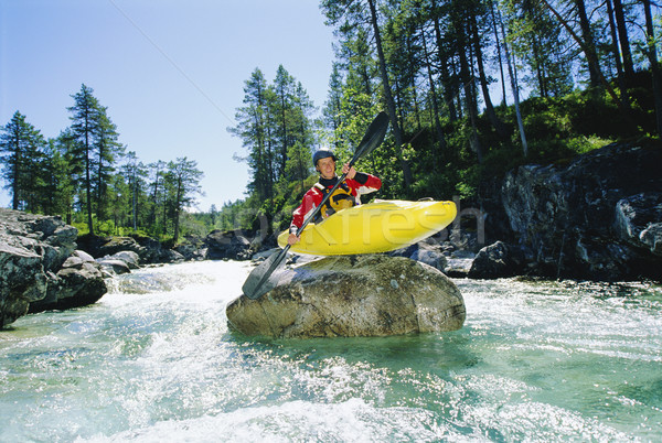 Stock photo: Kayaker perched on boulder in river