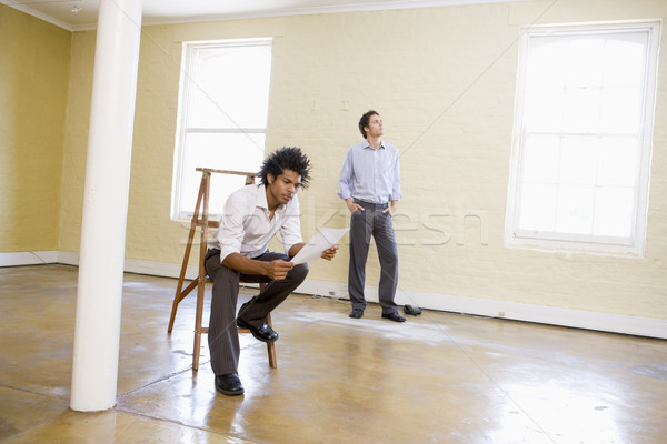 Man sitting on ladder in empty space holding paper with other ma Stock photo © monkey_business
