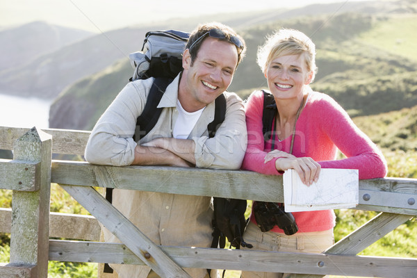 Stock photo: Couple on cliffside outdoors leaning on railing and smiling