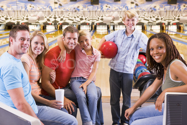 Family in bowling alley with two friends smiling Stock photo © monkey_business