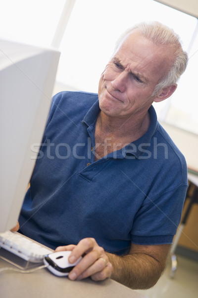 Mature male student frowning at computer monitor Stock photo © monkey_business