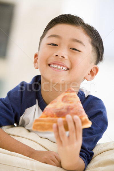 Young boy eating pizza slice in living room smiling Stock photo © monkey_business