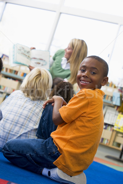 Kindergarten teacher reading to children in library, boy looking Stock photo © monkey_business