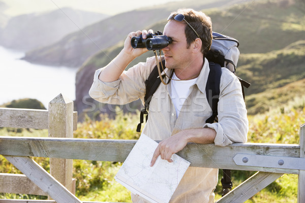 Man relaxing on cliffside path holding map and binoculars Stock photo © monkey_business
