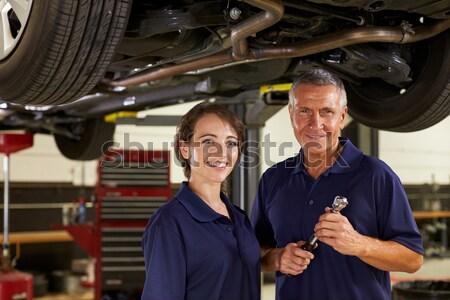Two mechanics standing in garage smiling Stock photo © monkey_business
