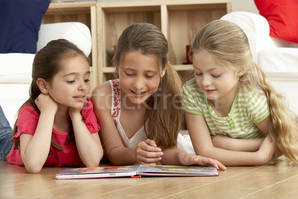 Stock photo: Three Young Girls Reading Book at Home