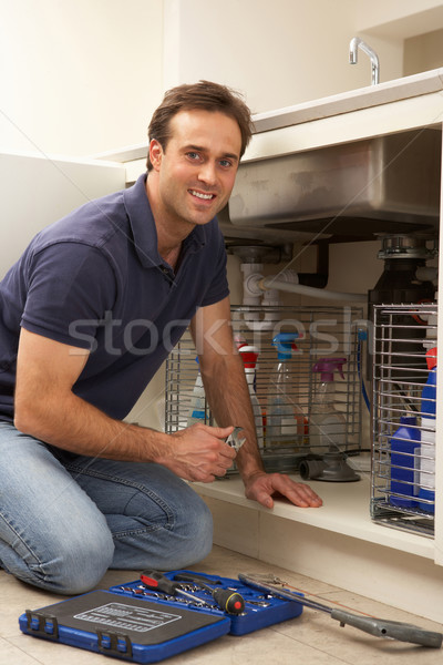 Plumber Working On Sink In Kitchen Stock photo © monkey_business