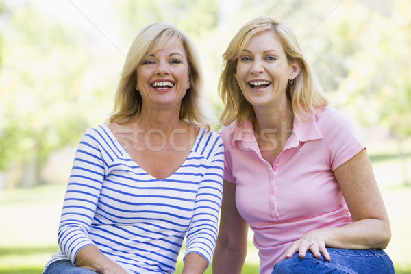 Two women sitting outdoors smiling Stock photo © monkey_business