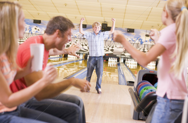 Family in bowling alley cheering and smiling Stock photo © monkey_business