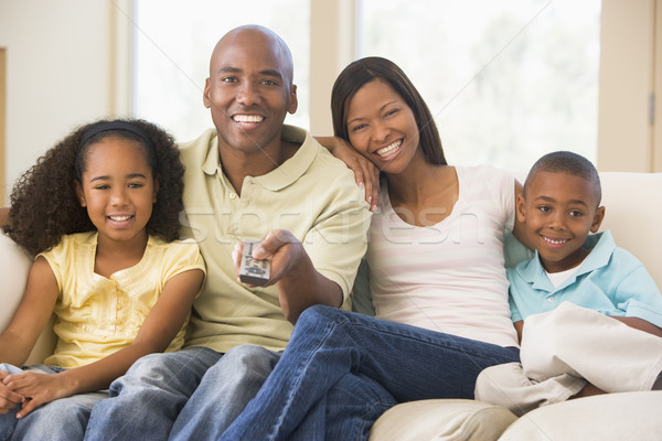 Family sitting in living room with remote control smiling Stock photo © monkey_business