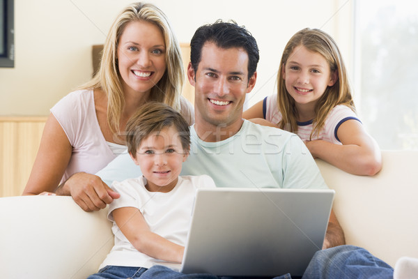 Stock photo: Family in living room with laptop smiling