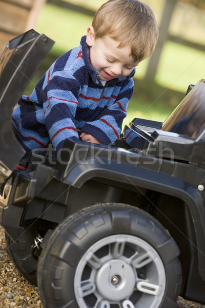 Young boy playing outdoors with toy truck smiling Stock photo © monkey_business