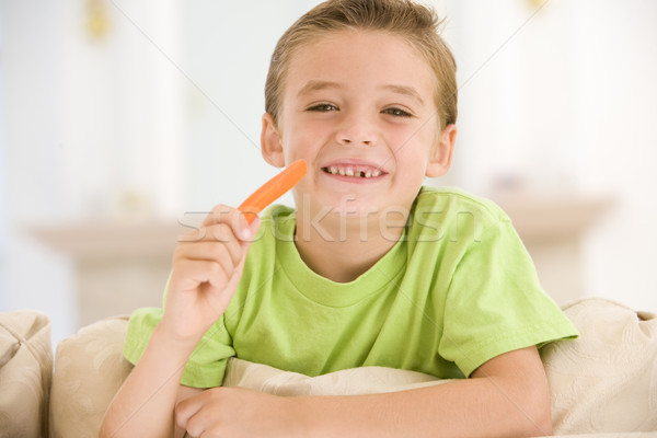 Young boy eating carrot stick in living room smiling Stock photo © monkey_business