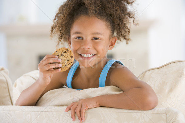 Young girl eating cookie in living room smiling Stock photo © monkey_business