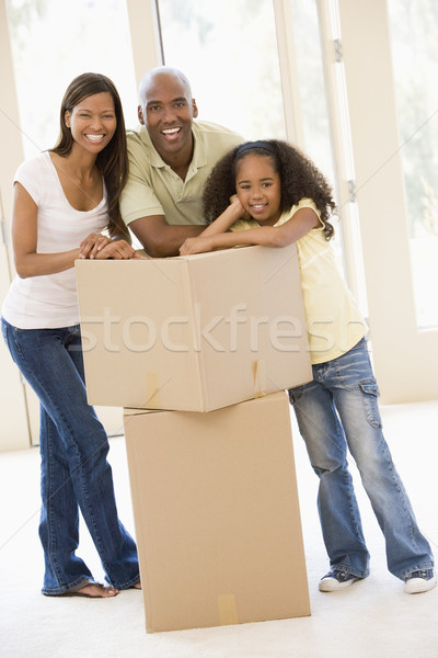 Family with boxes in new home smiling Stock photo © monkey_business