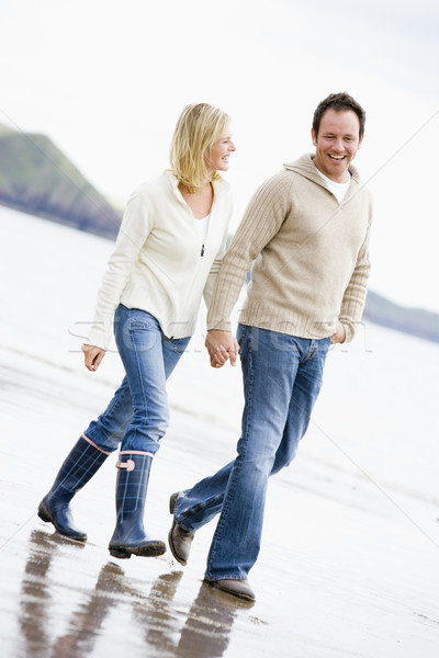 Couple walking on beach holding hands smiling Stock photo © monkey_business