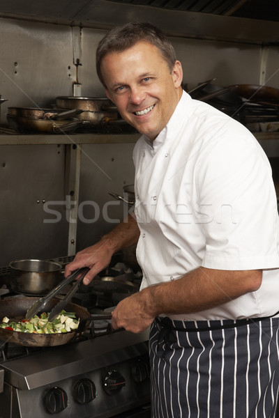 Male Chef Preparing Meal On Cooker In Restaurant Kitchen Stock photo © monkey_business