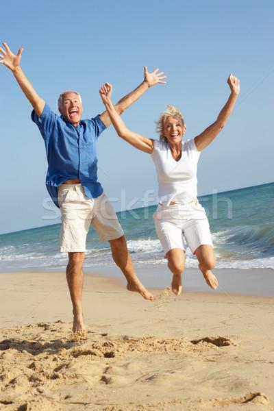 Senior Couple Enjoying Beach Holiday Jumping In Air Stock photo © monkey_business