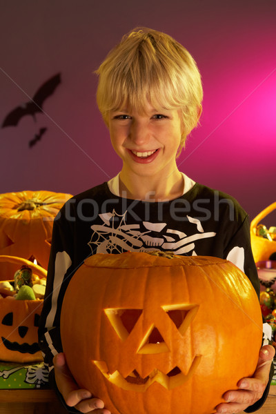 Halloween party with a boy holding carved pumpkin Stock photo © monkey_business