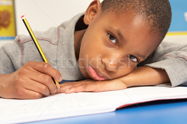 Unhappy Schoolboy Studying In Classroom Stock photo © monkey_business