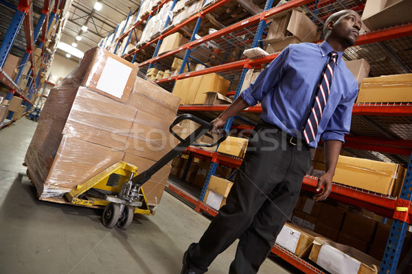 Man Pulling Pallet In Warehouse Stock photo © monkey_business