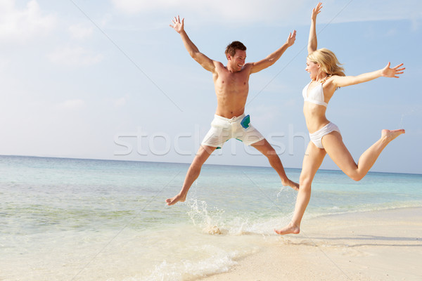 Couple Jumping In The Air On Tropical Beach Stock photo © monkey_business