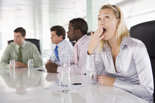 Four businesspeople in boardroom with one businesswoman yawning Stock photo © monkey_business