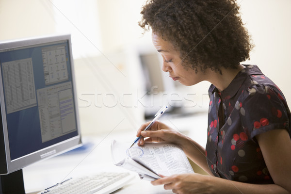 Woman in computer roon circling items in newspaper Stock photo © monkey_business