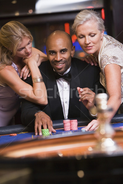 Man in casino with glamorous women Stock photo © monkey_business