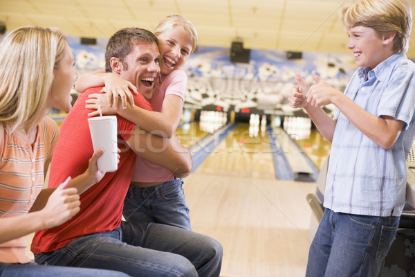 Stock photo: Family in bowling alley cheering and smiling