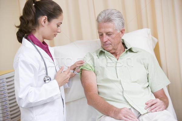 Doctor giving man needle in exam room Stock photo © monkey_business